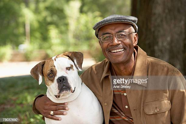 mature man embracing his bulldog outdoors, smiling, portrait - brown hat stock pictures, royalty-free photos & images