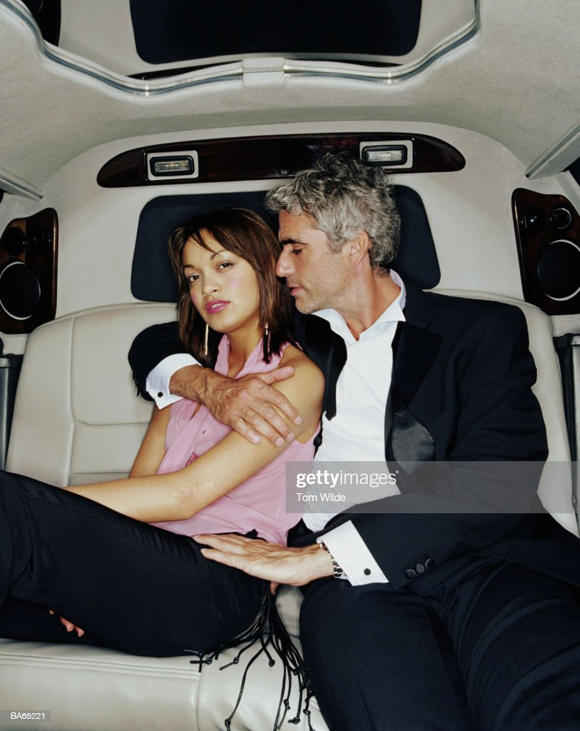 Mature man embracing young woman in back of limousine, portrait : Stock Photo