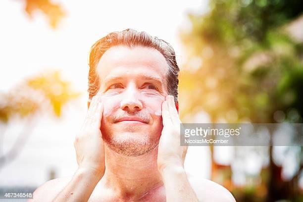 Mature man enjoying applying skin cream after sunburn