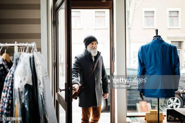 mature man entering clothing store - 入る ストックフォトと画像