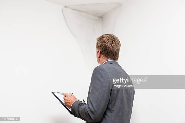 mature man examining damp patch on wall - damaged stock pictures, royalty-free photos & images