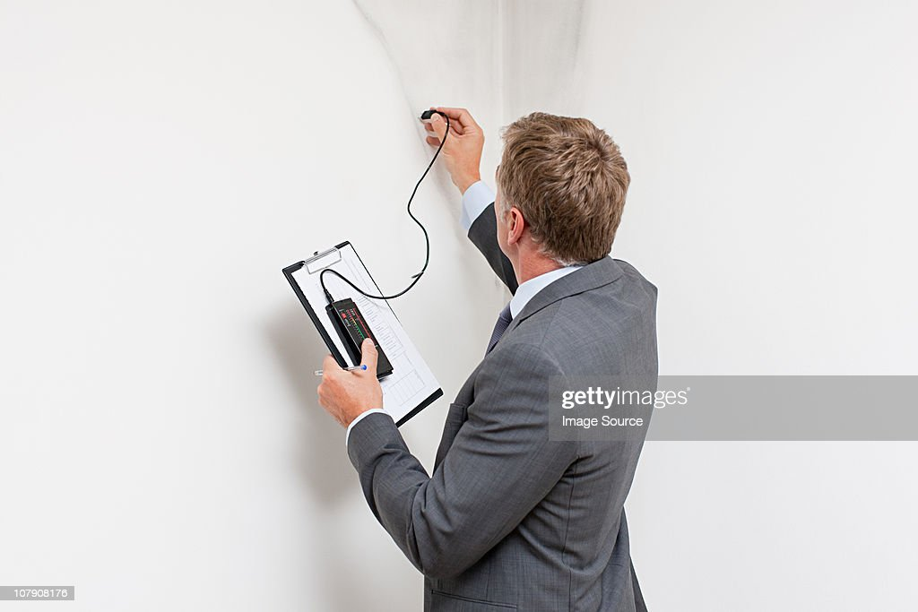 Mature man examining damp patch on wall : Stock Photo