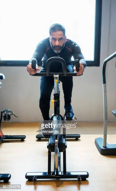 mature man exercising at gym - human limb stock pictures, royalty-free photos & images