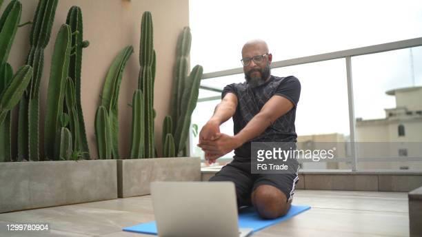 オンラインクラスを見ながら自宅で運動する成熟した男 - 自己改善 ストックフォトと画像
