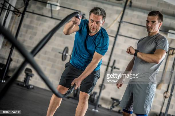mature man exercising in gym - sports training stock pictures, royalty-free photos & images