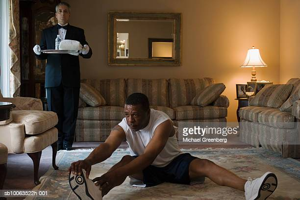 Mature man exercising on carpet, butler waiting with water on tray, in living room