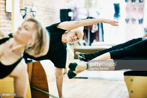 Mature man exercising on pilates chair during class in fitness studio