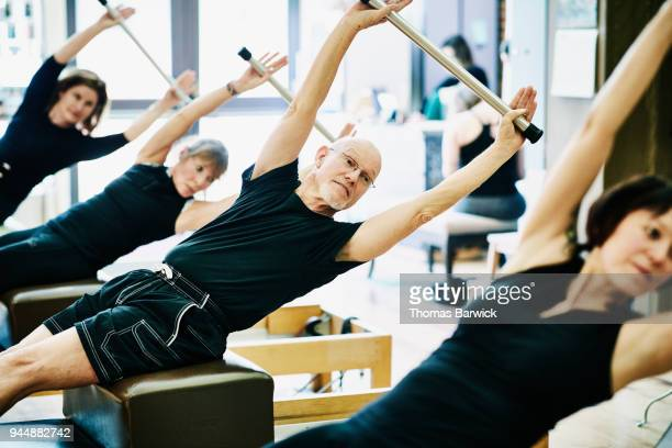 Mature man exercising on pilates reformer short box during class in fitness studio