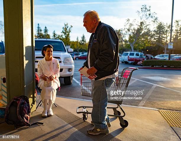 Mature man exiting a CVS pharmacy speaks to a young woman in uniform who smiles while soliciting holiday charitable donations, Walnut Creek,...
