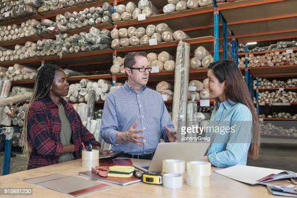 カーペット倉庫で 2 人の女性同僚に説明する中年の男性