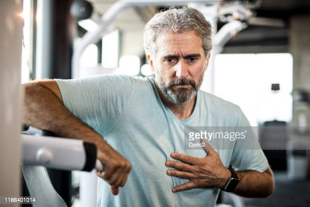 mature man feeling chest pain while exercising in a gym. - heart attack stock pictures, royalty-free photos & images