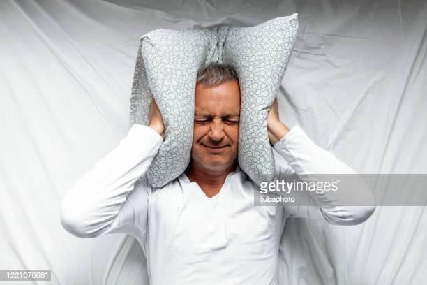 ベッドで不快に感じる成熟した男 - 音 ストックフォトと画像