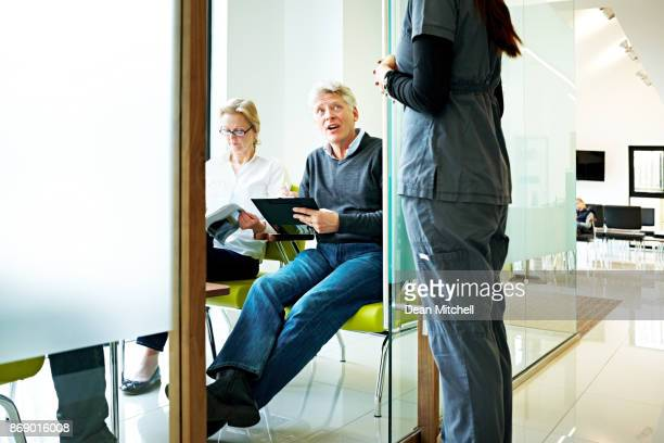 Mature man filling a form and talking with nurse