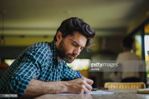 mature man filling in paperwork - authors stock pictures, royalty-free photos & images