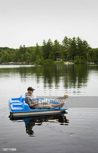 Mature man fishing on a lake with his dog