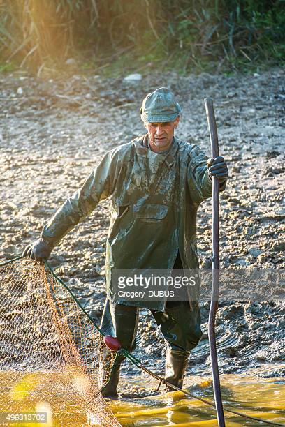 Mature man fishing with large net in french pond