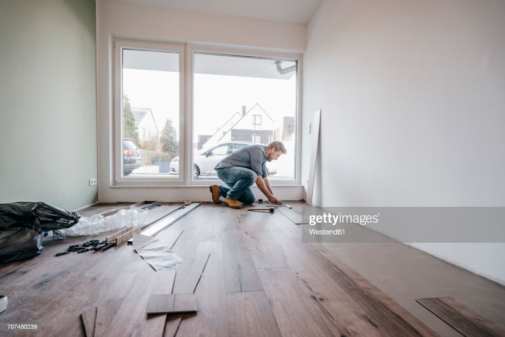 Mature man fitting flooring in new home : Stock Photo