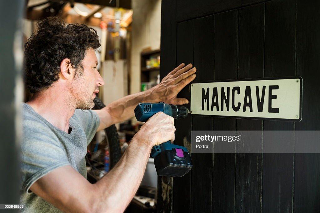 Mature man fixing mancave sign on wooden door : Stock Photo