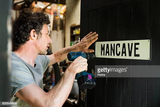 mature man fixing mancave sign on wooden door - nameplate stock pictures, royalty-free photos & images