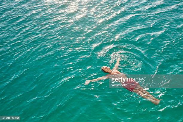 mature man floating in emerald water - smooth stock photos and pictures