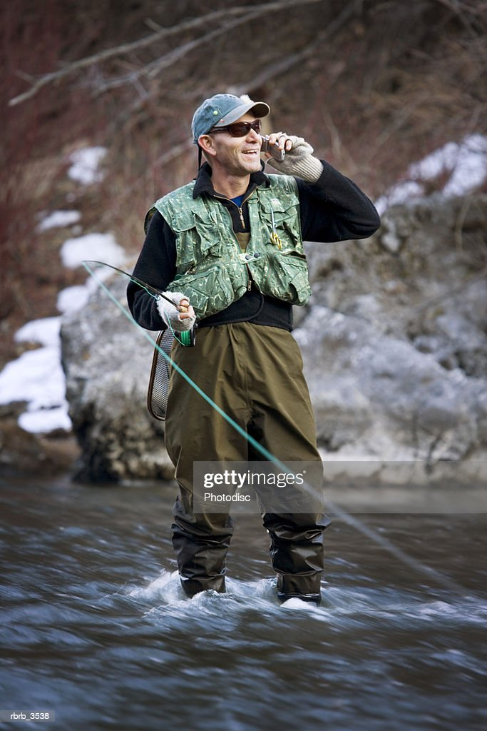 Mature man fly-fishing in a river : Stockfoto
