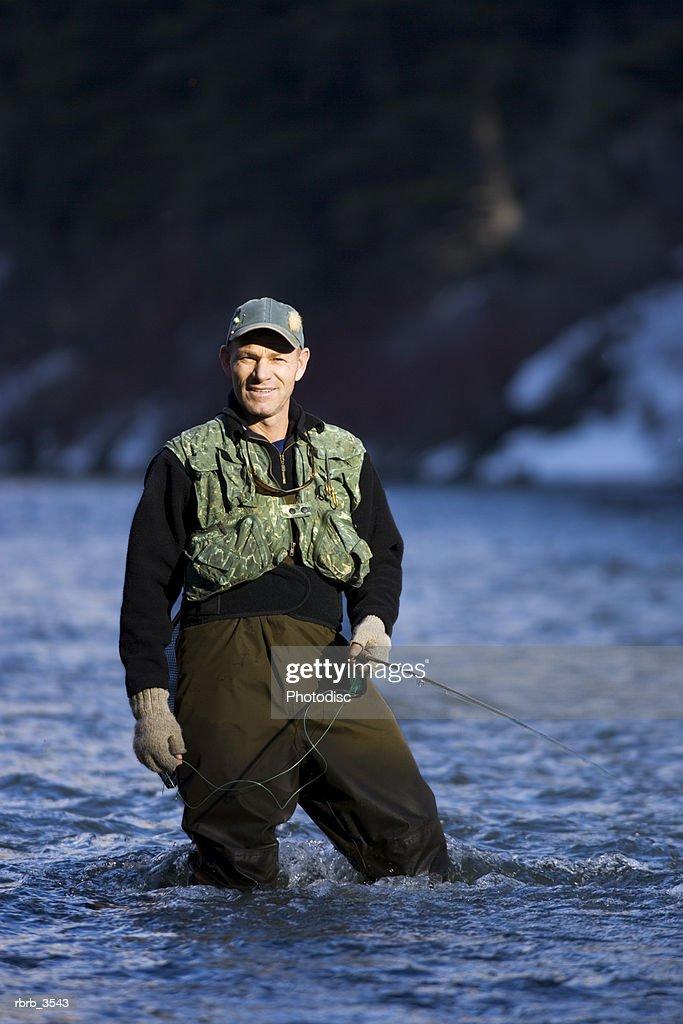 Mature man fly-fishing in a river : Foto de stock