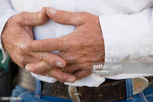 mature man folding hands over stomach, close-up, mid section - manos entrelazadas fotografías e imágenes de stock