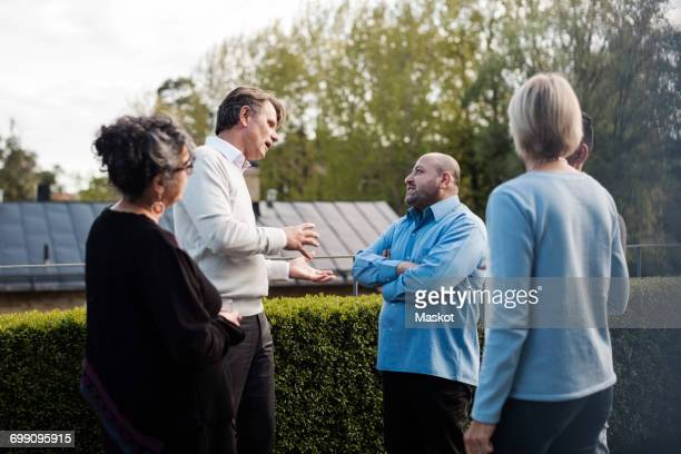Mature man gesturing while talking to friends by hedge in yard