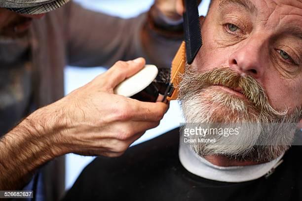 Mature man getting his beard trimmed