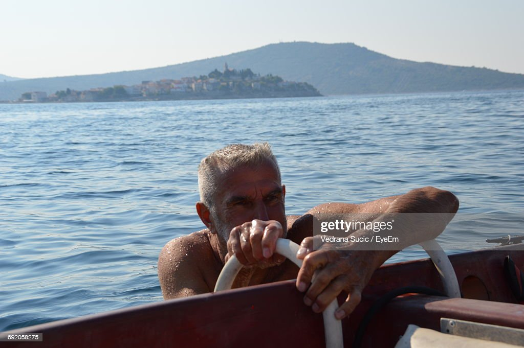 Mature Man Getting On Boat Against Clear Sky : Stock Photo