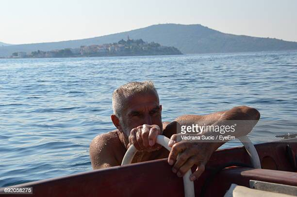 Mature Man Getting On Boat Against Clear Sky
