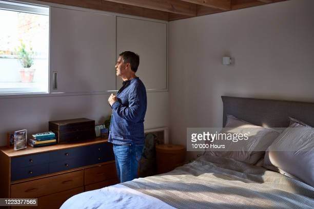 mature man getting ready in bedroom - routine stock pictures, royalty-free photos & images