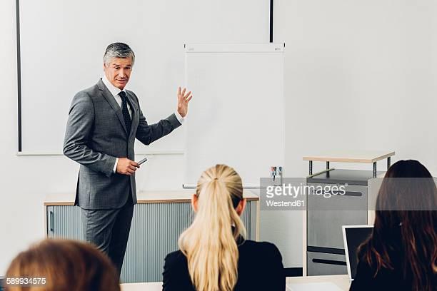 mature man giving business presentation - セールストーク ストックフォトと画像