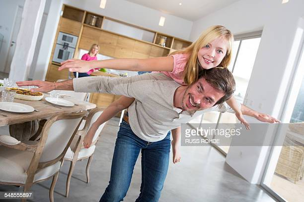 Mature man giving daughter piggy back in dining room