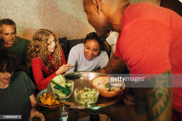 mature man giving food to family and friends during sporting event - spectator stock pictures, royalty-free photos & images