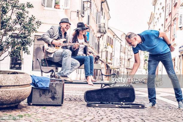 mature man giving money to street artists - guitar case stock pictures, royalty-free photos & images