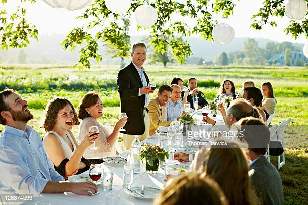 Mature man giving toast at outdoor banquet table