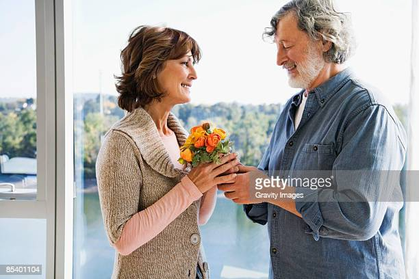 Mature man giving women a bunch of wild flowers