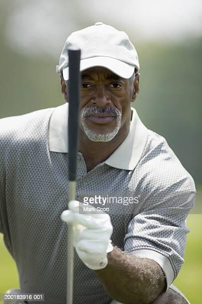 Mature man golfing,  lining up putt