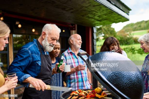 mature man grilling vegetables at garden party - mature men stock pictures, royalty-free photos & images