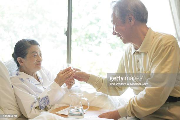 Mature man handing a glass of water to mature woman