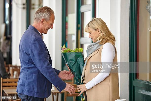 Mature man handing date bouquet at sidewalk cafe table
