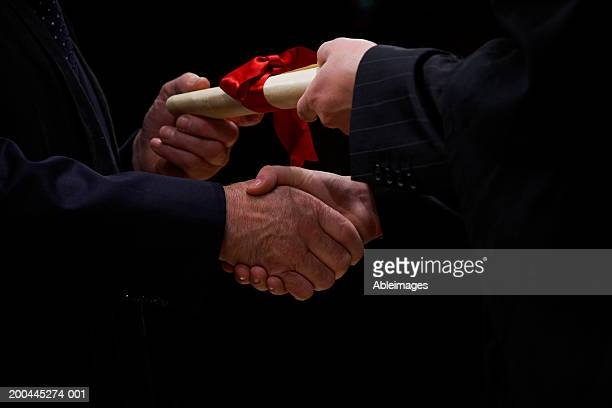 mature man handing scroll to young man, shaking hands, close-up - 紙製備品 ストックフォトと画像