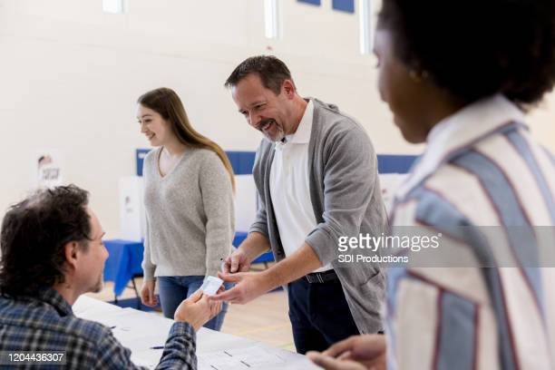 mature man hands id to polling place volunteer - id card stock pictures, royalty-free photos & images