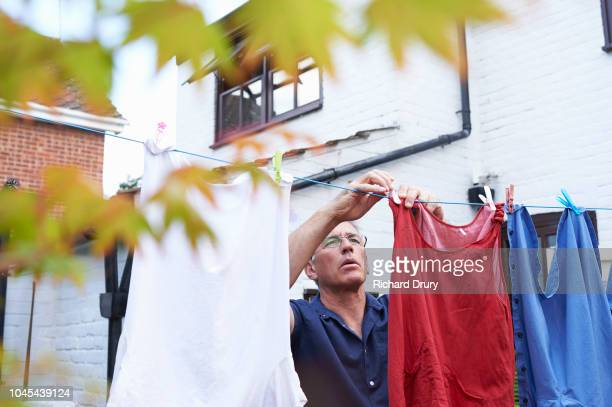 mature man hanging clothing on the washing line - richard drury stock pictures, royalty-free photos & images