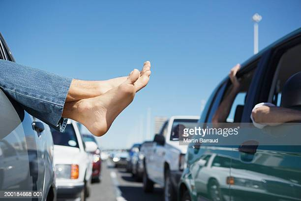 Mature man hanging feet outside of car window in traffic jam, close-up