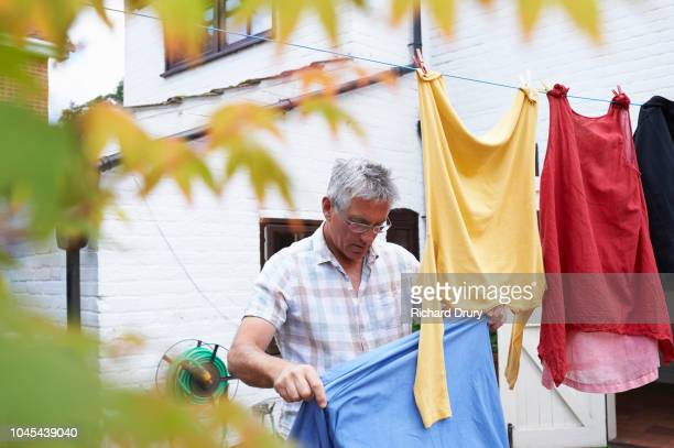 mature man hanging out clothing on the washing line - richard drury stock pictures, royalty-free photos & images