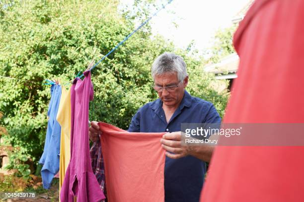 mature man hanging out the washing on the washing line - richard drury stock pictures, royalty-free photos & images