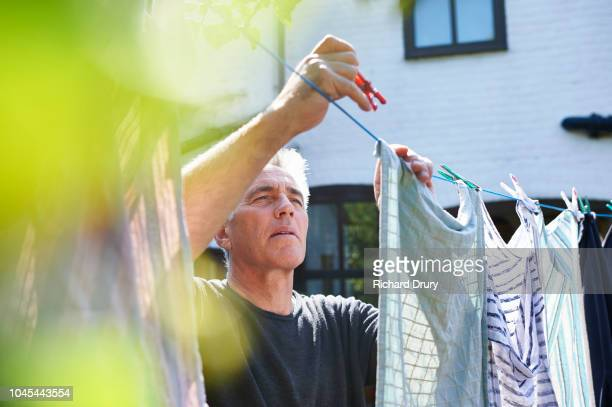 mature man hanging out the washing on the washing line - hanging stock pictures, royalty-free photos & images