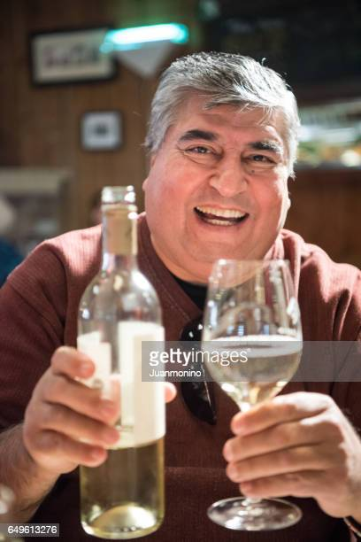 Mature man having a glass of wine in a tavern